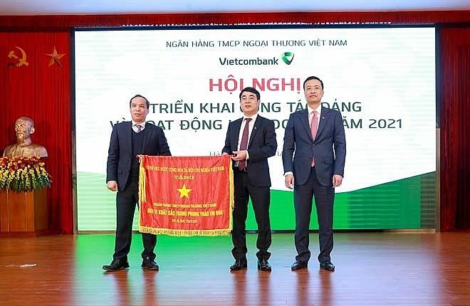 : Thừa ủy quyền của Thủ tướng Chính phủ, Phó Thống đốc NHNN Đoàn Thái Sơn trao Cờ thi đua của Thủ tướng Chính phủ cho Vietcombank tại Hội nghị triển khai hoạt động kinh doanh năm 2021 của Vietcombank