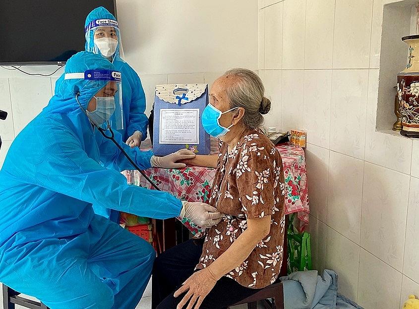 Cán bộ y tế kiểm tra sức khỏe người cao tuổi có bệnh lí nền tại Trạm Y tế lưu động.